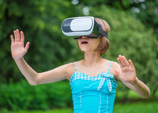 Niña con los vidrios de VR en parque Imagen de archivo