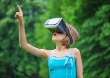 Niña con los vidrios de VR en parque Imagen de archivo libre de regalías