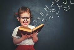 Niña con los vidrios que lee un libro con las letras de salida Imagen de archivo libre de regalías