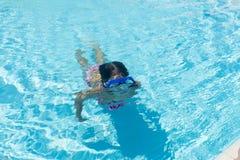 Niña con los vidrios que se zambullen azules en una piscina al aire libre Imagen de archivo libre de regalías