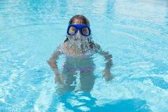 Niña con los vidrios que se zambullen azules en una piscina al aire libre Imagen de archivo