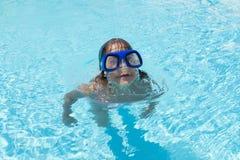 Niña con los vidrios que se zambullen azules en una piscina al aire libre Fotografía de archivo