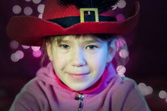 Niña con mirada del sombrero con las luces de la Navidad Imágenes de archivo libres de regalías