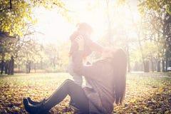 Niña con su madre que juega en parque foto de archivo