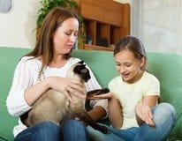 Niña con su madre y gato siamés Foto de archivo libre de regalías
