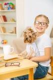 Niña con su perro en el escritorio Fotografía de archivo