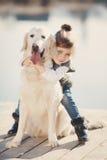 Niña con su perro querido en el lago Foto de archivo