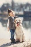 Niña con su perro querido en el lago Foto de archivo libre de regalías