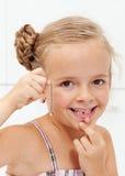 Niña con su primer diente de leche que falta Imagenes de archivo