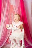 Niña con un bebé de la palabra en falda rosada Fotografía de archivo