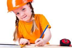 Niña con un casco de la construcción Foto de archivo libre de regalías