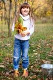 Niña con un compartimiento y las hojas de arce Fotografía de archivo