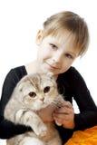 Niña con un gato en un fondo blanco Fotografía de archivo