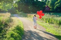 Niña con un manojo de globos rojos fotografía de archivo libre de regalías