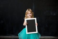 niña con un marco en sus manos Imagen de archivo