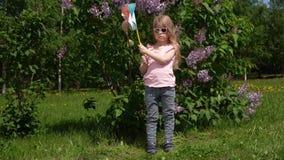 Niña con un molinillo de viento en un parque al lado de una lila floreciente en la primavera almacen de video