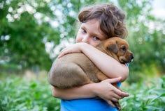 Niña con un perrito en sus brazos Imagen de archivo