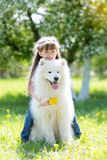 Niña con un perro blanco grande en el parque Fotos de archivo libres de regalías