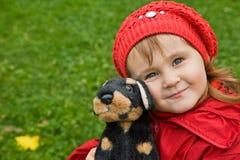 Niña con un perro de juguete en parque Imagen de archivo libre de regalías