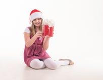 Niña con un regalo en un sombrero de Papá Noel Imagenes de archivo