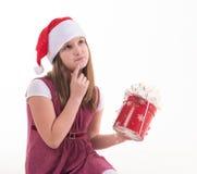 Niña con un regalo en un sombrero de Papá Noel Imagen de archivo