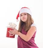 Niña con un regalo en un sombrero de Papá Noel Foto de archivo