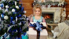Niña con un retrato del regalo del bebé lindo con el regalo de Navidad en sus manos, distribuyendo el regalo del ` s del Año Nuev metrajes