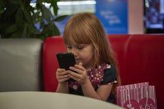 Niña con un smartphone en café Imagenes de archivo