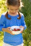 Niña con un tazón de fuente de fresas imágenes de archivo libres de regalías