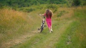 Niña con una bicicleta en naturaleza metrajes