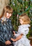 Niña con una madre embarazada en el árbol de navidad en casa Imagen de archivo