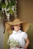 niña con una sonrisa en un sombrero de paja de ala ancha en un ramo de lirios blancos del valle en las manos Imagen de archivo