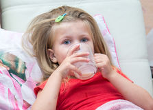 Niña con una taza de leche Foto de archivo