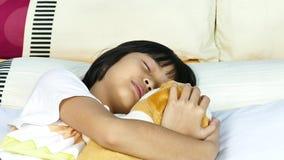 Niña de Asia que duerme en la cama que abraza el oso de peluche metrajes
