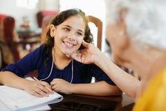 Niña de ayuda de la mujer mayor que hace la preparación de la escuela Imagen de archivo libre de regalías