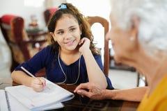 Niña de ayuda de la mujer mayor que hace la preparación de la escuela Fotos de archivo libres de regalías