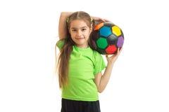 Niña de Cutie con el balón de fútbol multicolor en manos Imagen de archivo libre de regalías