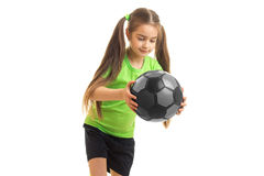 Niña de Cutie en uniforme del verde con el balón de fútbol en manos Imagen de archivo libre de regalías
