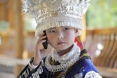 Niña de la nacionalidad de Miao con el teléfono móvil Foto de archivo libre de regalías