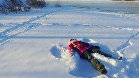 Niña de la vista lateral que hace ángel de la nieve Niño del invierno Día de invierno soleado almacen de video