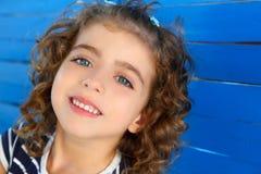 Niña de los niños que sonríe en la pared azul de madera Fotografía de archivo