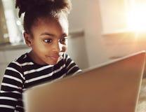 Niña de moda que usa un ordenador portátil en casa Fotografía de archivo libre de regalías