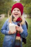 Niña de risa que sostiene la taza del cacao con las melcochas afuera Fotografía de archivo libre de regalías