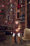 Niña debajo del árbol en la Navidad Imagen de archivo
