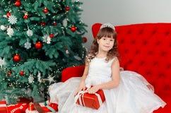Niña debajo del árbol en la Navidad Fotos de archivo