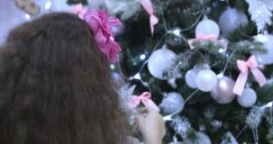 Niña del CU con el pelo rizado en un vestido festivo, decoraciones colgantes de la Navidad en el árbol de navidad con la Navidad metrajes