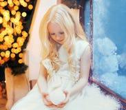 Niña del niño con el juguete de la bola de nieve sobre hogar del bokeh del árbol de navidad cerca de la ventana Fotos de archivo libres de regalías