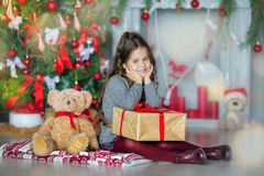 Niña del niño con la caja de regalo cerca del árbol de navidad y de la chimenea en casa Imagen de archivo