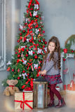 Niña del niño con la caja de regalo cerca del árbol de navidad y de la chimenea en casa Fotografía de archivo