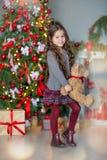Niña del niño con la caja de regalo cerca del árbol de navidad y de la chimenea en casa Fotografía de archivo libre de regalías
